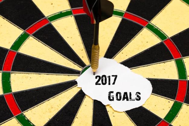 2017 doelen. darten met dartpijl die op een vel papier was gespeld voor labels