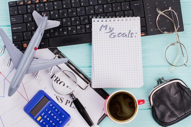 2018 doelen op notebook met reiziger accessoires bril portemonnee en vliegtuig op houten tafelblad achtergrond. plat lag reisconcept.