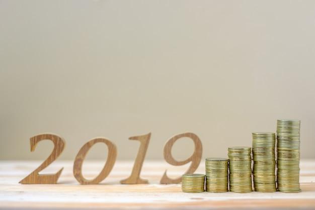 2019 gelukkig nieuwjaar met gouden munten stapel en houten nummer