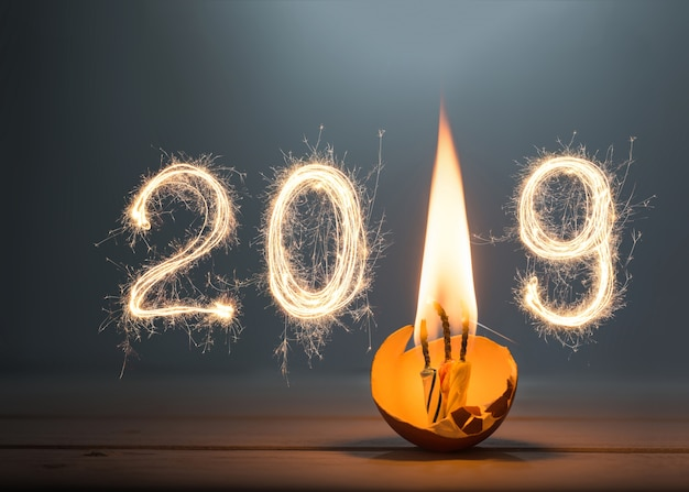 2019 geschreven met fonkelingsvuurwerk met verjaardagskaars, gelukkig nieuw jaar 2019 concept.