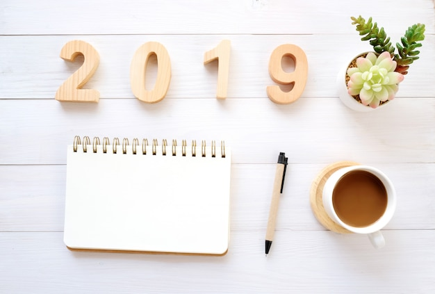 2019 houten brieven, leeg notitieboekjedocument en koffie op witte lijstachtergrond