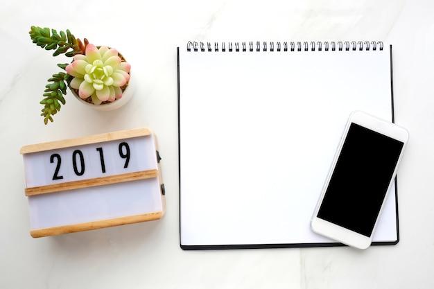 2019 houten kist, leeg notitieboekjespapier, slimme telefoon met leeg scherm