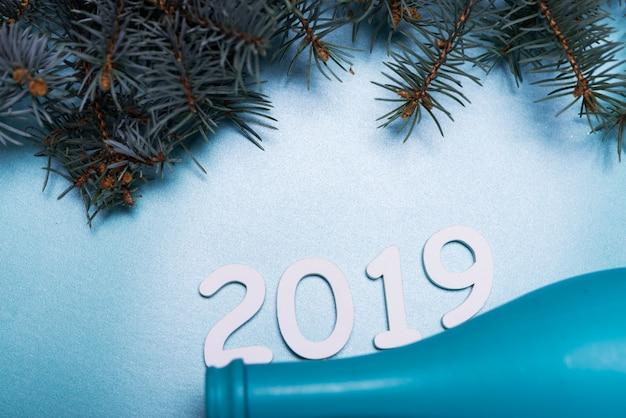 2019 inscriptie met blauwe fles op tafel