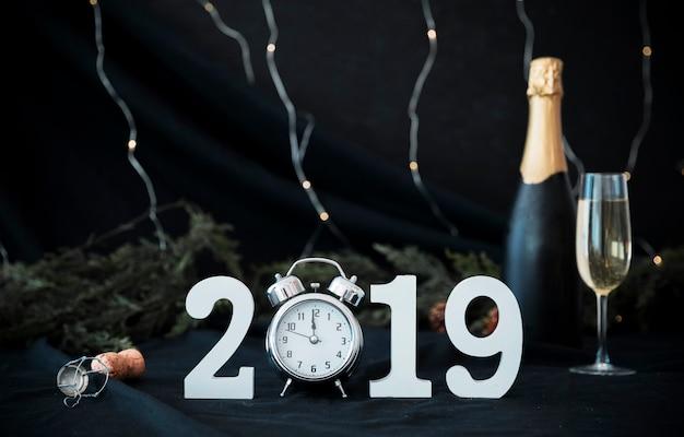 2019 inscriptie met klok en fles op tafel