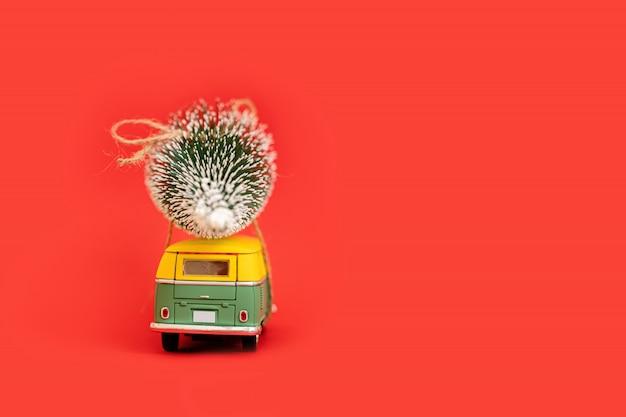 2019 miniatuur hippie auto met fir tree op rode achtergrond