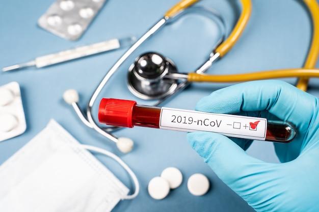 2019-ncov. de arts houdt een reageerbuis met bloed in zijn hand. een positieve bloedtest voor een nieuw coronavirus.
