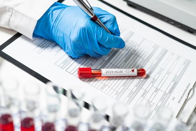 2019-ncov. een bloedbuis met de naam van een nieuwe stam van coronavirus 2019-ncov tegen een formulier voor het registreren van patiëntgegevens. doctor's werkplek