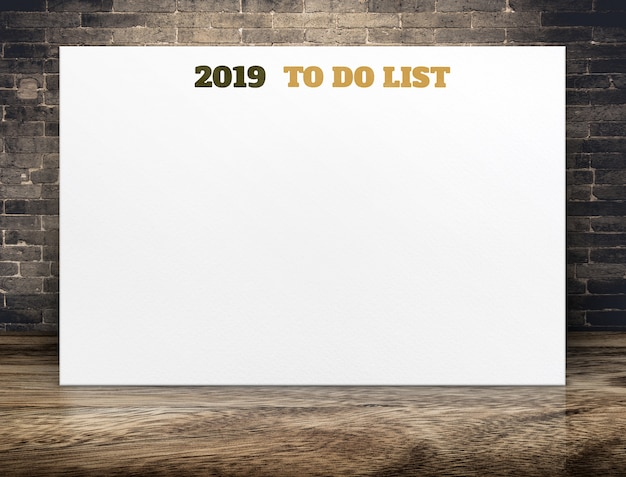 2019 nieuw jaar om lijst op witboekaffiche op bruine houten vloerruimte en bakstenen muur te doen