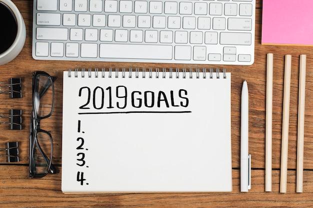 2019 nieuwjaarsdoel, plan, actie tekst op blocnote met bureautoebehoren.