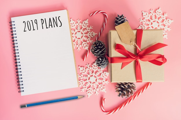 2019 nieuwjaarsplannen, bruine geschenkdoos, notitieblok en kerstdecoratie