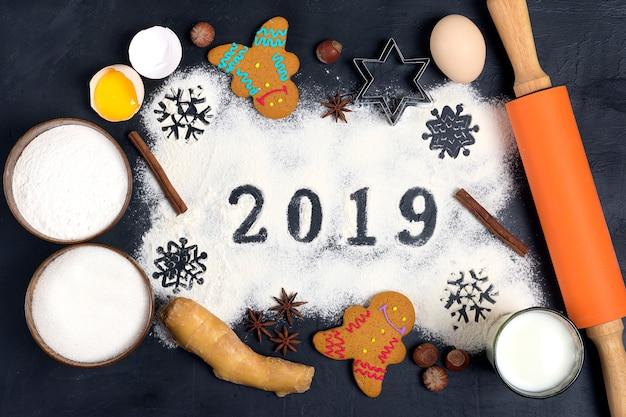 2019 tekst gemaakt met meel met decoraties op zwarte achtergrond met peperkoek kerstmis