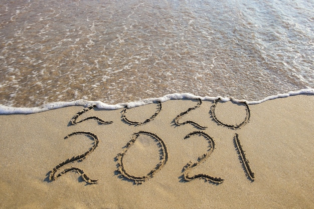 2020, 2021 jaar geschreven op zandstrand zee