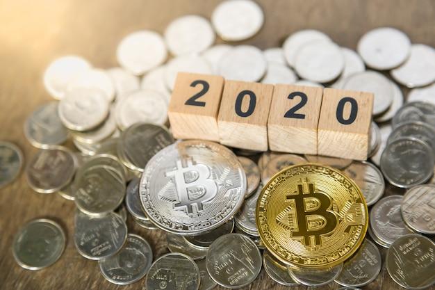 2020, business, geld en cryptocurrency concept. sluit omhoog van zilveren en gouden bitcoin op stapel van zilveren muntstukken en het houten stuk speelgoed van het aantalblok.