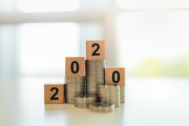 2020-concept. sluit omhoog van het houten stuk speelgoed van het aantalblok bovenop stapel muntstukken.