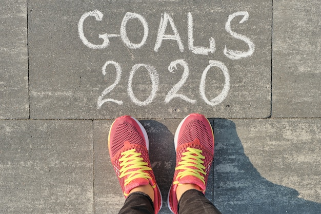 2020-doelen geschreven op grijze stoep met benen van de vrouw in sneakers