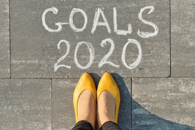 2020-doelen geschreven op grijze stoep met een vrouw ervoor