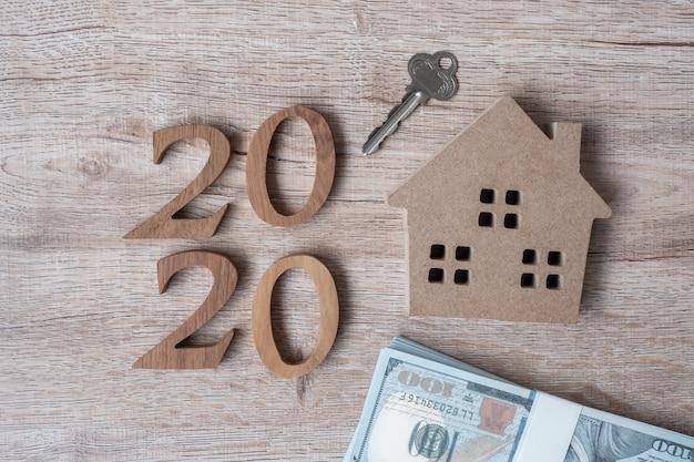 2020 gelukkig nieuwjaar met huismodel en geld op houten achtergrond.