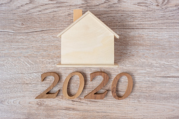2020 gelukkig nieuwjaar met huismodel op houten tafel