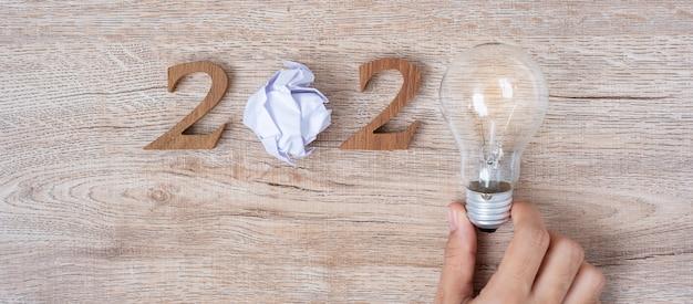 2020 gelukkig nieuwjaar met zakenman die gloeilamp met afgebrokkeld papier houdt