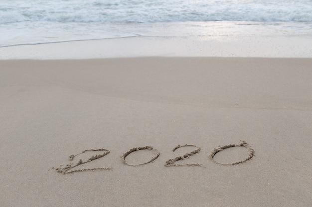 2020 geschreven in het zand op het strand voor het nieuwe jaar