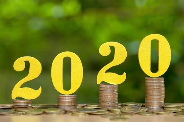2020 houten nummers op gestapelde munten met financiële groei, geld besparen
