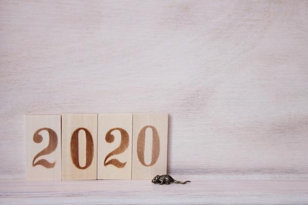 2020 met houten figuren op het houten oppervlak en een kleine metalen muis