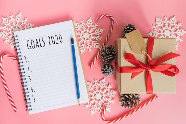 2020 nieuw jaarconcept. doelstellingen 2020 lijst in kladblok, geschenkdoos en kerstdecoratie op roze pastelkleur met kopie ruimte