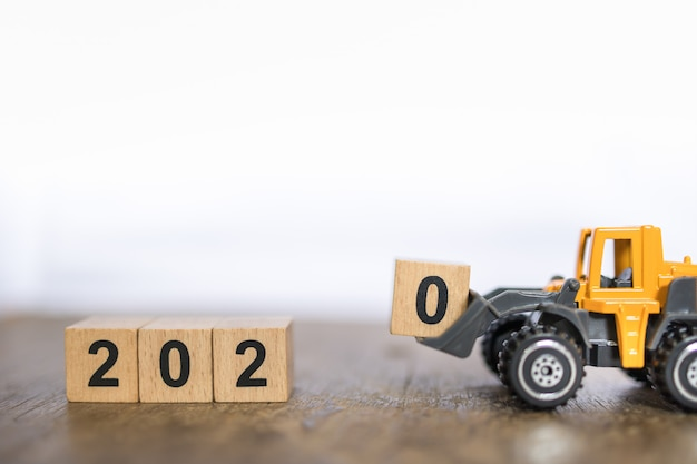 2020 nieuw jaarconcept. sluit omhoog van stuk speelgoed de machineauto van de ladervrachtwagen geladen nummer 0 houten blokstuk speelgoed op houten lijst en exemplaarruimte