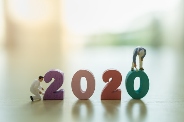 2020 nieuwjaar, bedrijfs- en planningsconcept. sluit omhoog van groep arbeiders miniatuurcijfer die en kleurrijk houten aantal met exemplaarruimte schilderen schoonmaken