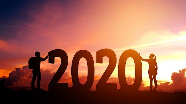 2020 nieuwjaar couple probeert het aantal 2020 gelukkig nieuwjaar te pushen