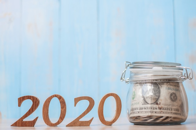2020 nieuwjaar met geld glazen pot en houten nummer.