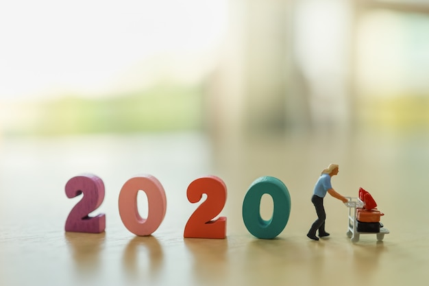 2020 nieuwjaar reisplanning concept. mensen miniatuurcijfermensen met luchthaventrolley (bagagekar).