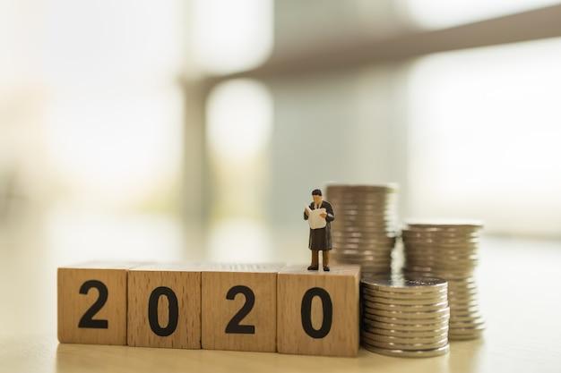 2020 nieuwjaarsconcept. sluit omhoog van zakenman miniatuurcijfer die en krant op het houten stuk speelgoed van het aantalblok met stapel muntstukken op houten lijst met exemplaarruimte bevinden zich lezen