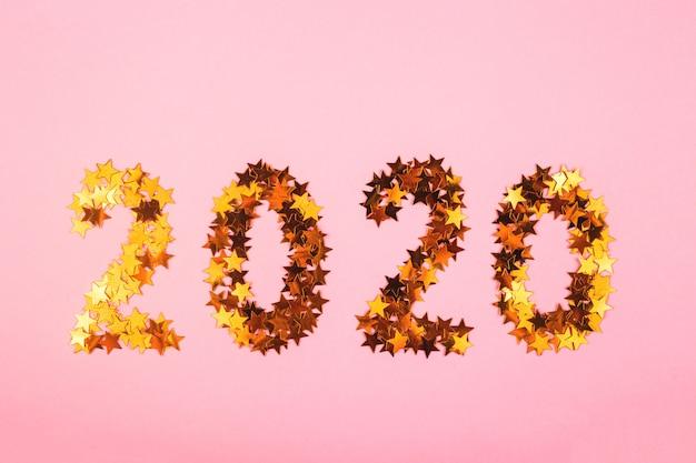 2020 nieuwjaarssymbool van gouden confetti op roze achtergrond.