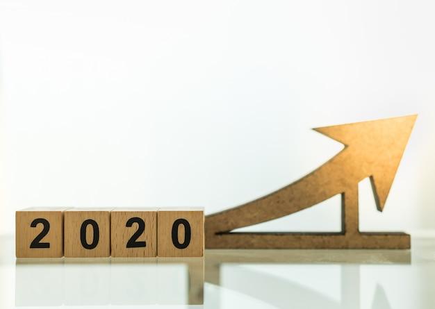 2020 planning, business en doel concept. sluit omhoog van houten aantalblokken met het houten diecut van het pijlpictogram met exemplaarruimte.