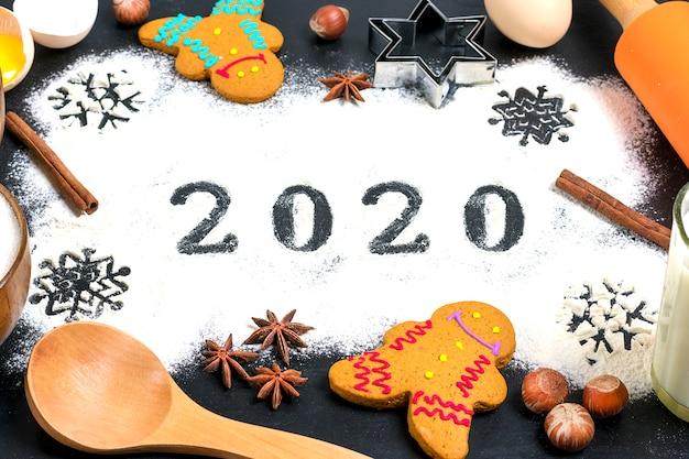 2020-tekst gemaakt met bloem met decoraties op een zwarte achtergrond.