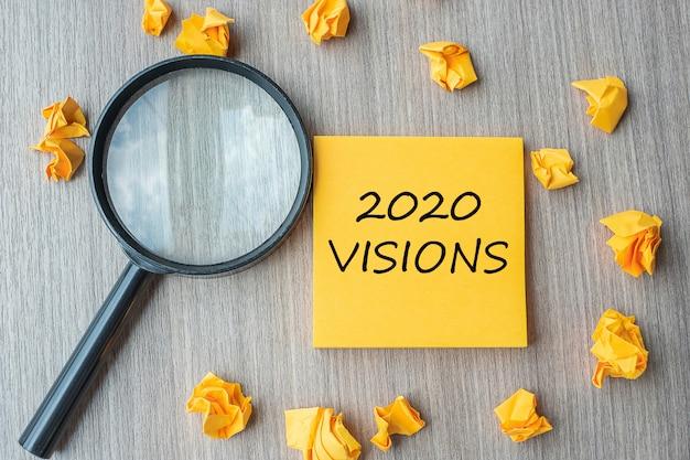 2020 visies woorden op gele notitie met verkruimeld papier