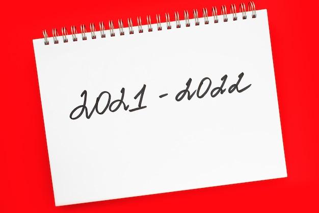 2021-2022 nieuw schooljaar. handgeschreven inscriptie in witte blocnote, op levendige rode achtergrond. plat lag, bovenaanzicht. terug naar schoolconcept.