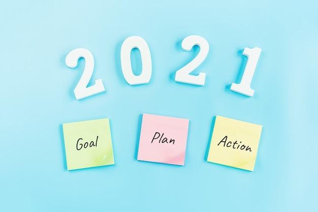2021 doel, plan en actie plaknotities op blauw, bovenaanzicht met kopie ruimte