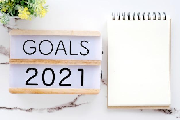2021-doelen op houten doos en blanco notitieboekpapier op wit marmer