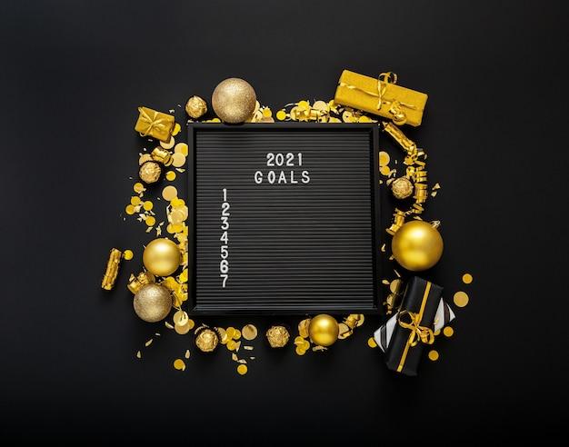 2021 doellijst op zwart letterbord in frame gemaakt van gouden kerstfeestdecor.