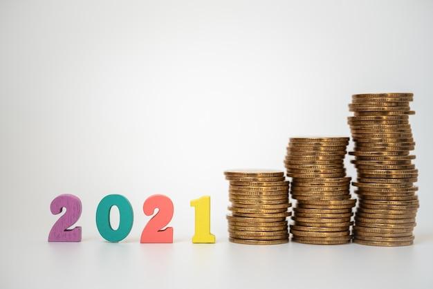 2021 geld, zaken en planning concept. kleurrijke houten cijferbrief met onstabiele stapel gouden muntstukken op witte achtergrond.