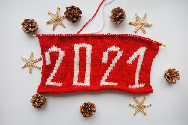 2021 gelukkig nieuwjaar. gebreid nummer. en stro sneeuwvlokken, dennenappel op witte achtergrond. hoge kwaliteit foto