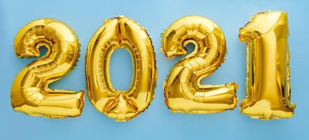 2021 gelukkig nieuwjaar gouden lucht ballonnen tekst in lijn op blauwe achtergrond.