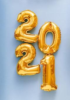 2021 gelukkig nieuwjaar gouden lucht ballonnen tekst op blauw oppervlak