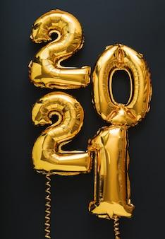 2021 gelukkig nieuwjaar gouden lucht ballonnen tekst op zwart verticaal formaat.
