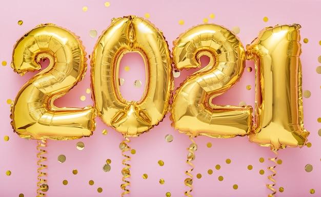 2021 gelukkig nieuwjaar gouden luchtballonnen op linten met confetti op roze muur.