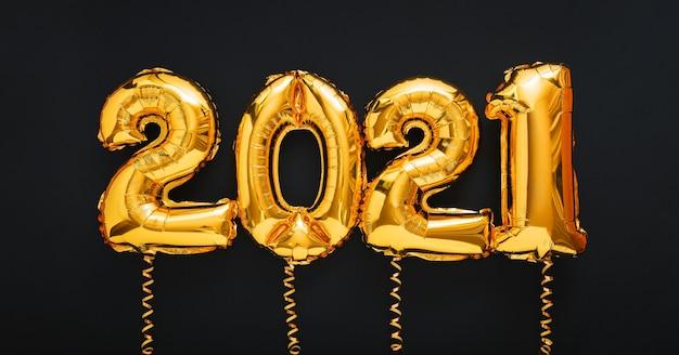2021 gelukkig nieuwjaar gouden luchtballonnen tekst in lijn met linten op zwart.
