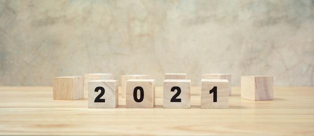 2021 gelukkig nieuwjaar op hout blok op houten tafel ang grijze achtergrond. nieuw jaar concept.