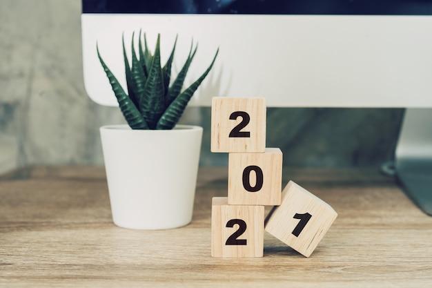 2021 gelukkig nieuwjaar op houten blok op houten tafel desktop computer en potplant. nieuw jaar concept